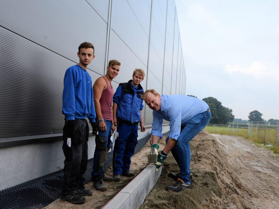 Stegemann unterstützt und zwei weitere Lehrlinge beim Verlegen der Bordsteine - Peter Wessels (3.v.l) prüft, ob die Arbeiten ordnungsgemäß erfolgen